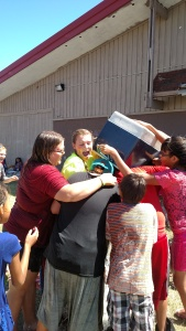 A group of kids using a cooler to soak the staff, our youth, and other kids...it was crazy and fun!