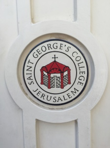 The seal of the college on the front doors.