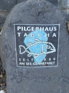 The logo of the Pilgerhaus on a rock outside the front doors.
