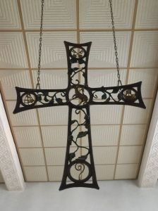 The cross hanging above the altar on the second level.
